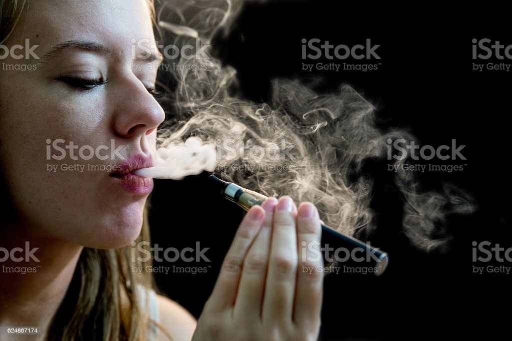 Elegant woman holding and smoking e-cigarette stock photo