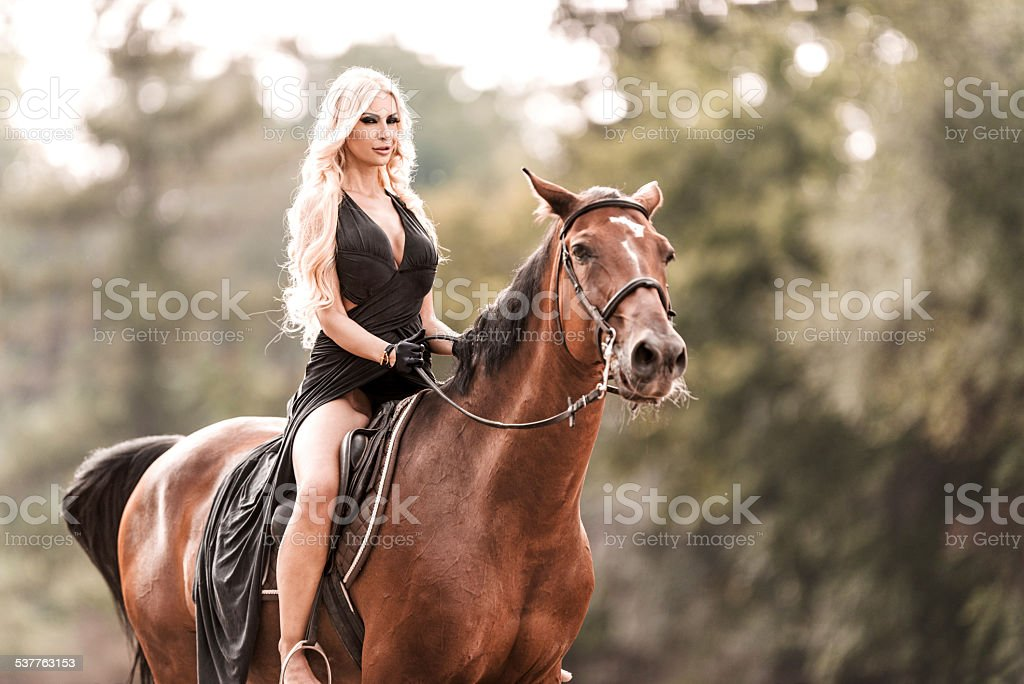 Elegant woman horseback riding. stock photo