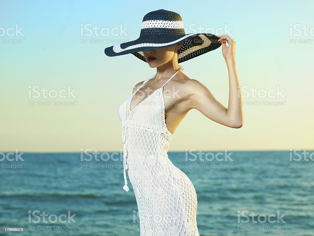 Elegant woman in a hat at sea stock photo