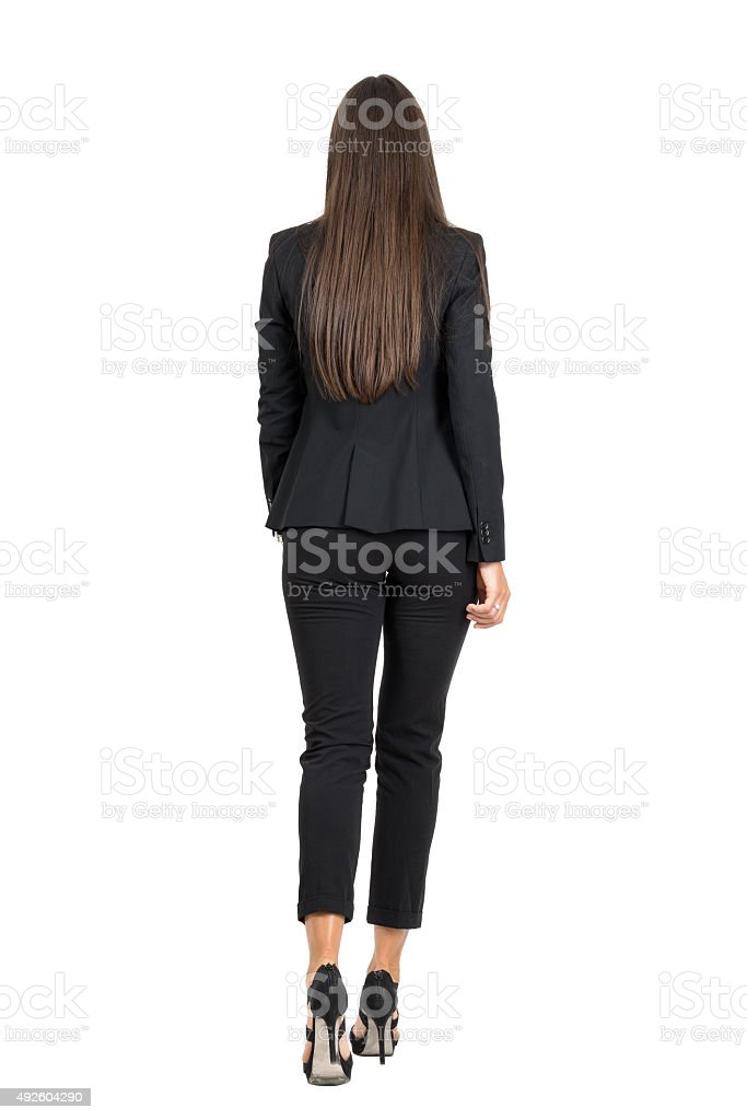 Elegant woman in business black suit walking away. Rear view stock photo