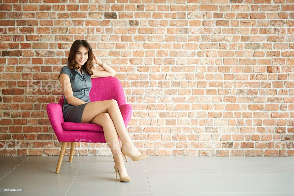 Elegant woman in the pink armchair stock photo