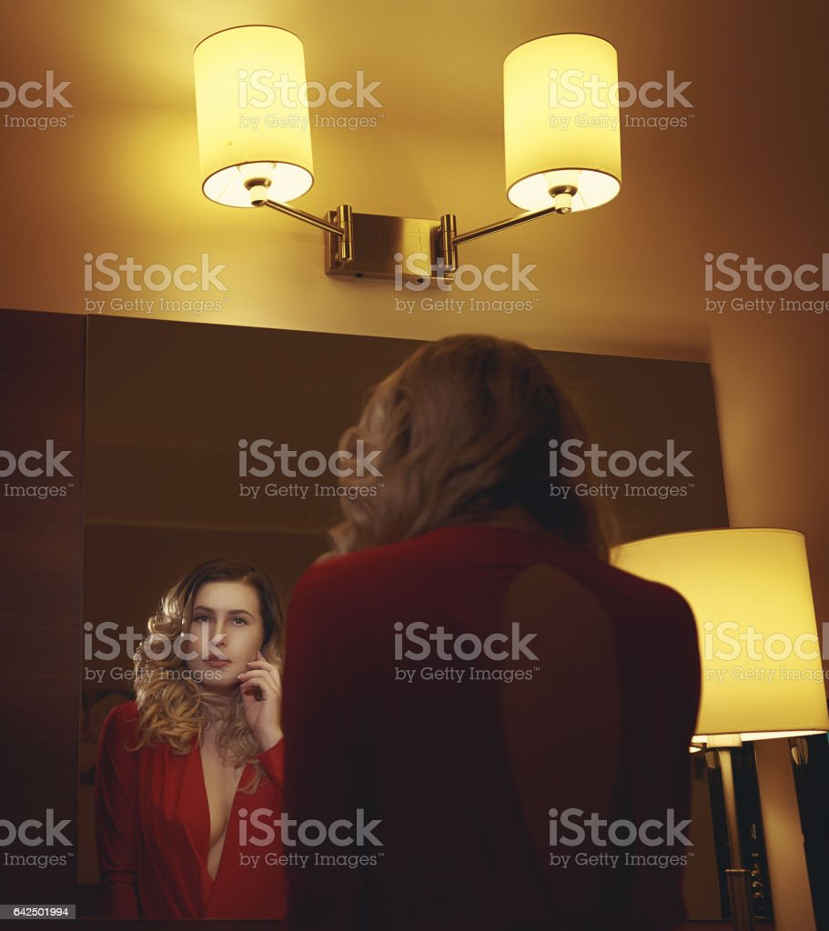 elegant woman looking in the mirror stock photo