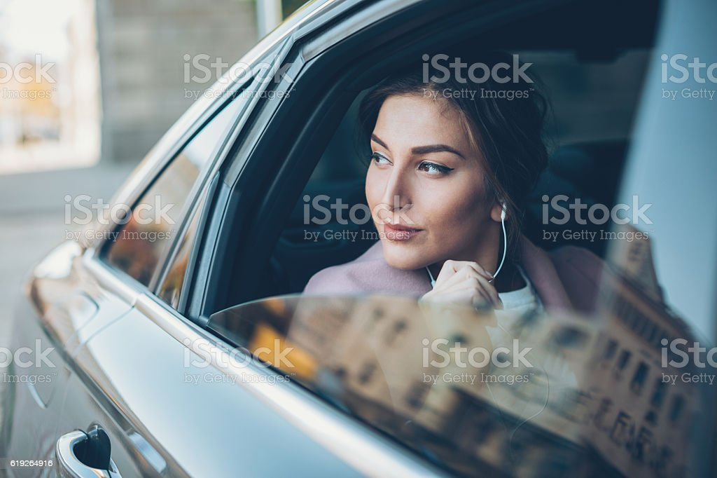 Elegant woman looking out of a car window stock photo