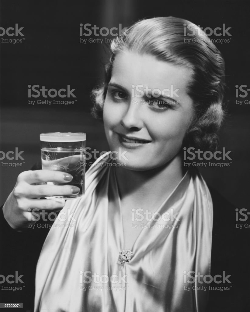 Elegant woman raising glass of water, posing in studio, (B&W), close-up, portrait stock photo