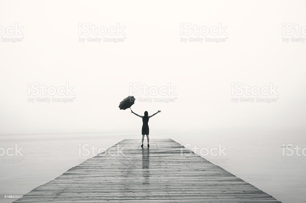 elegant woman rejoices with their arms up in the rain stock photo