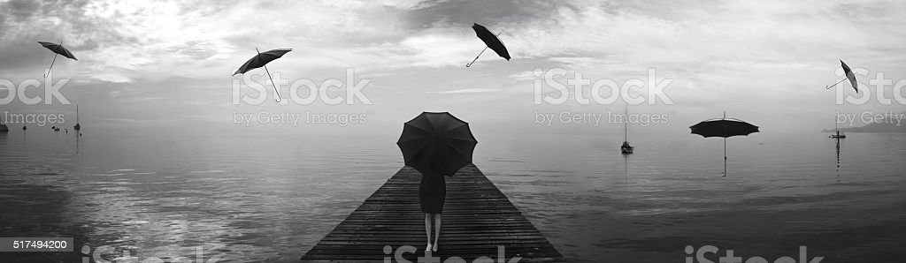 elegant woman repairing from the rain of blacks umbrellas stock photo