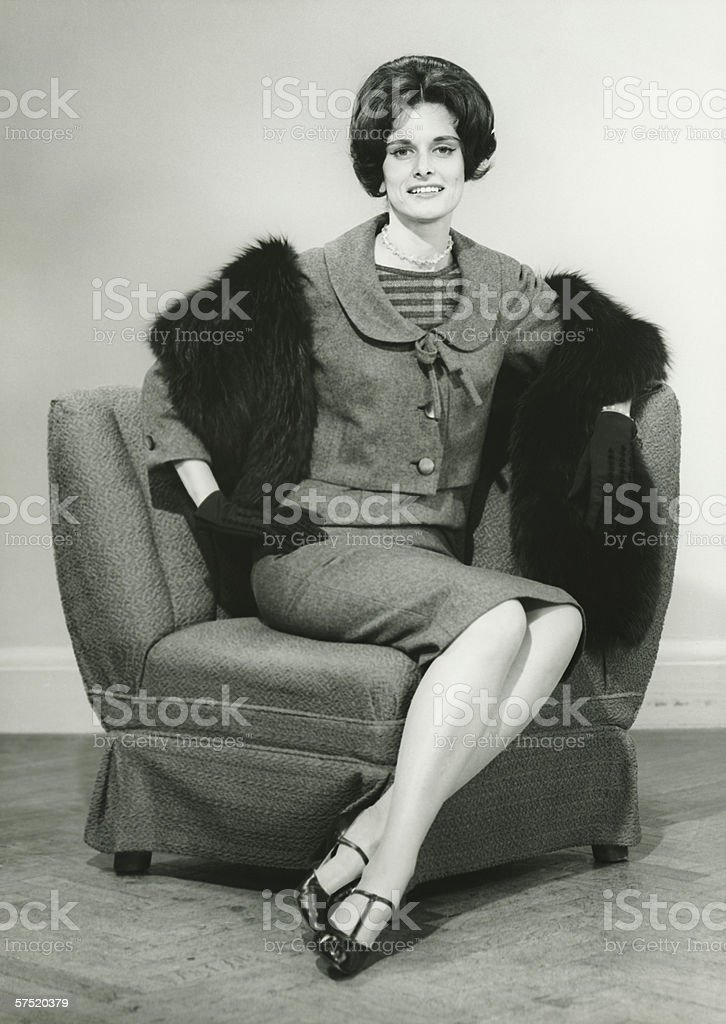 Elegant woman sitting on arm chair in studio, (B&W), portrait stock photo
