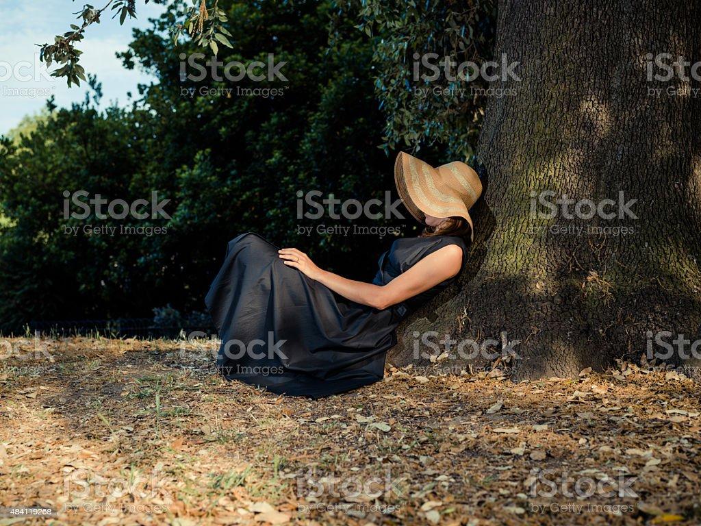 Elegant woman sitting under tree stock photo