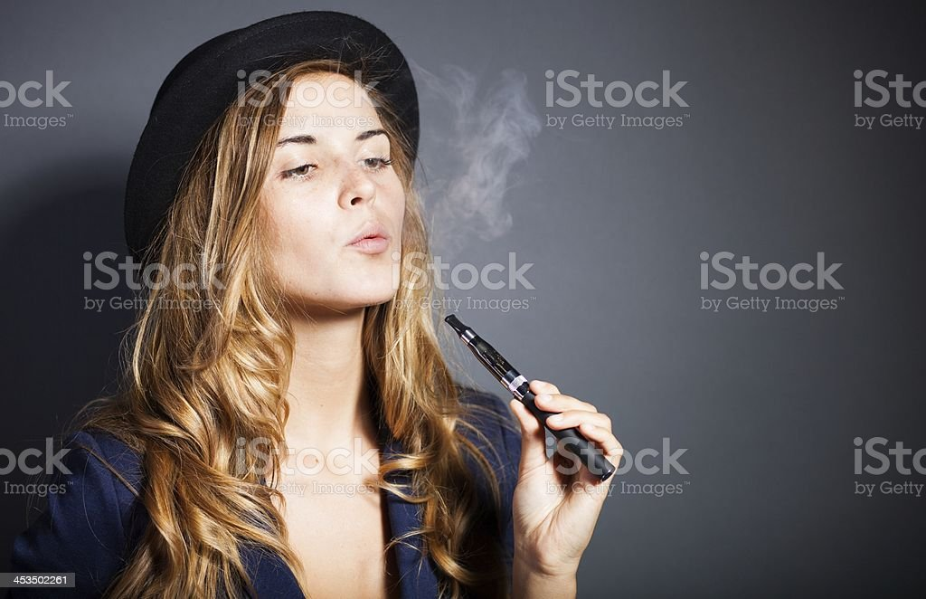 Elegant woman smoking e-cigarette with smoke wearing suit and hat stock photo