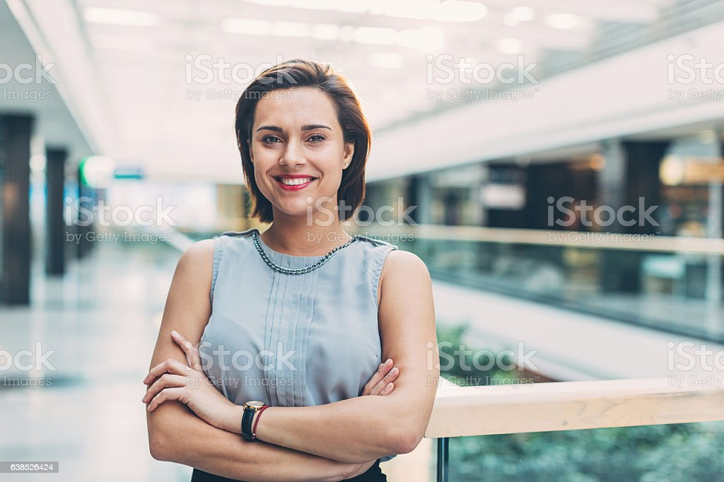 Elegant woman standing inside of business building stock photo