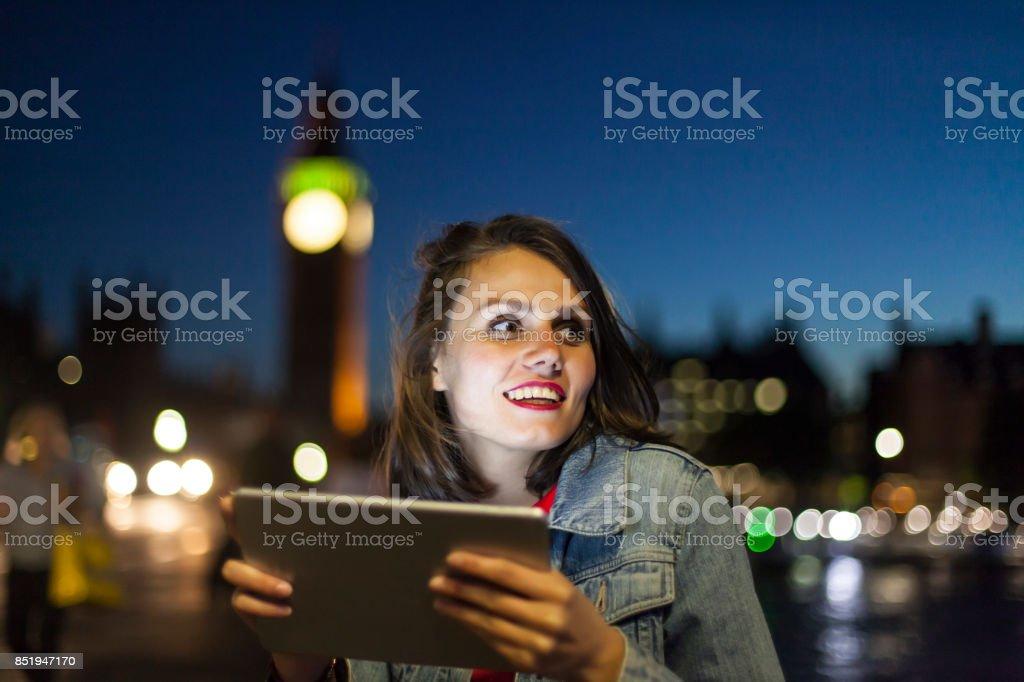 Elegant woman using digital tablet at night stock photo