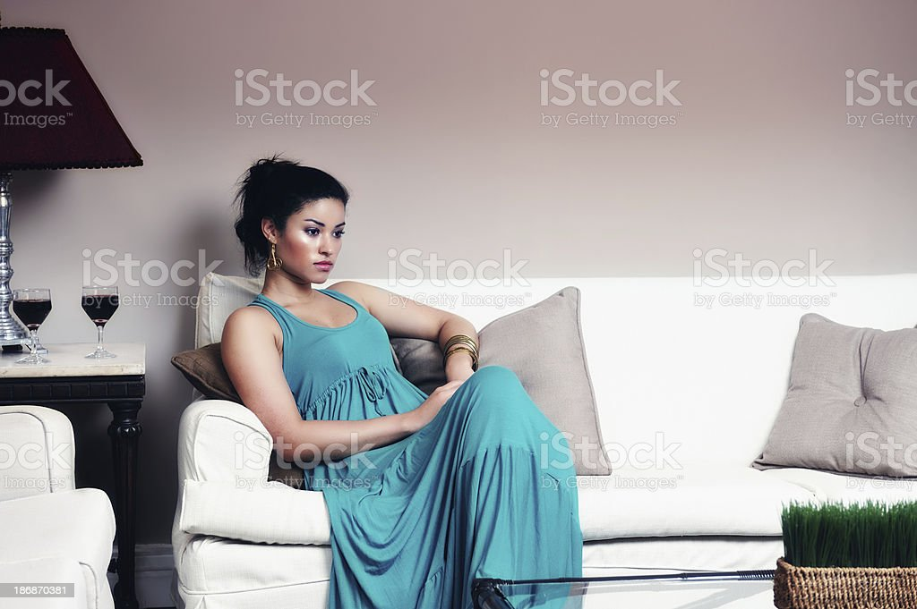 Elegant woman waiting on a couch royalty-free stock photo