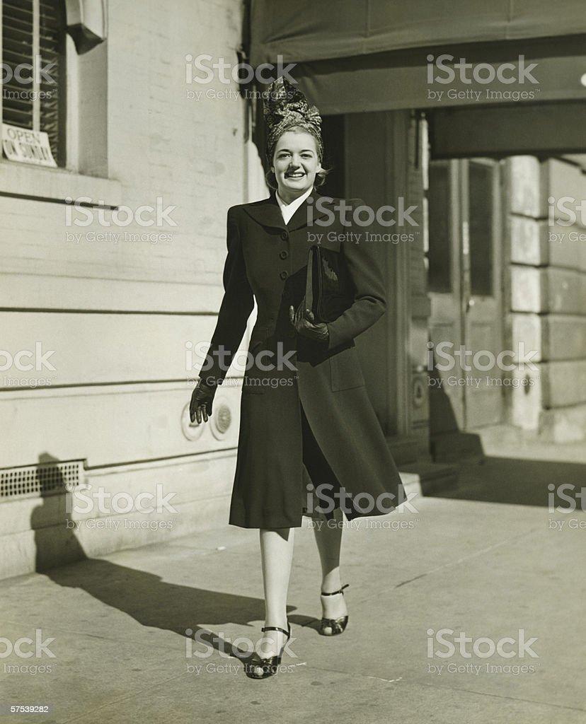 Elegant woman walking on sidewalk, (B&W) stock photo