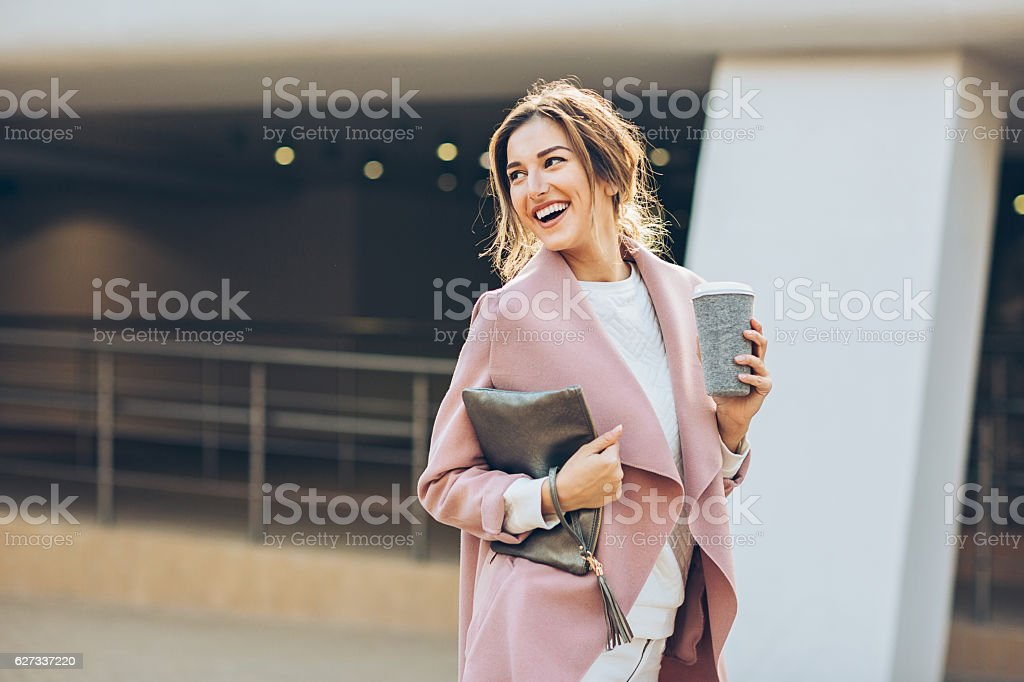 Elegant woman walking outdoors and looking back stock photo
