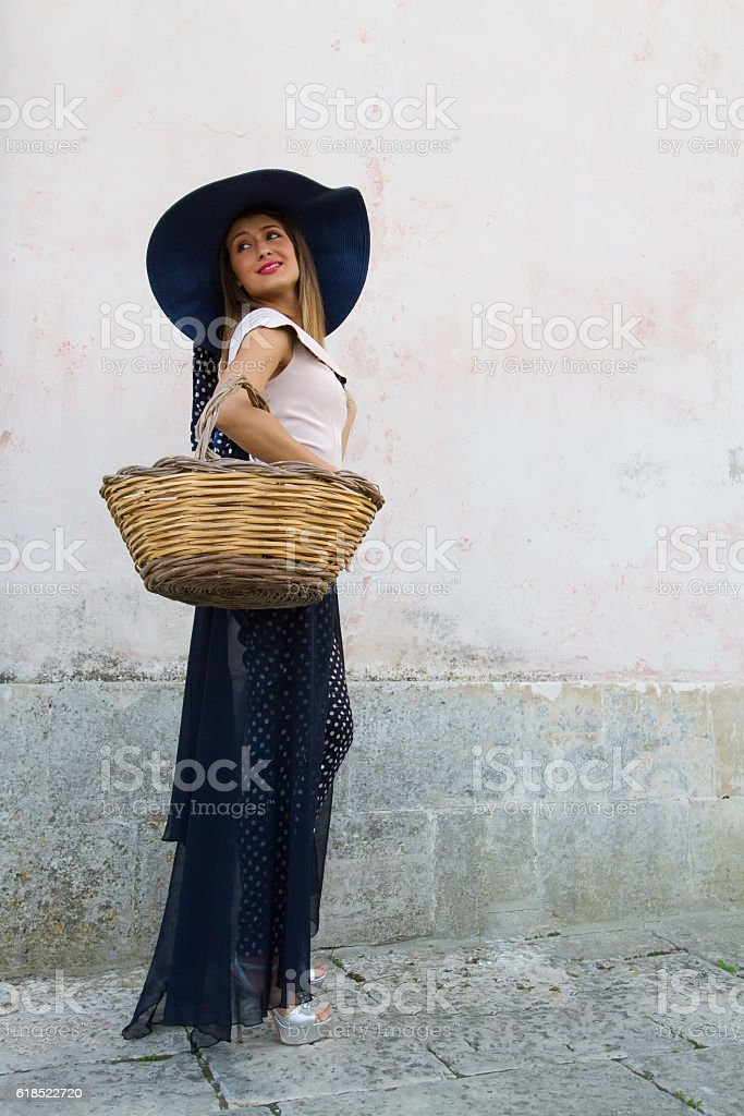 Elegant Woman with Sunhat and Wicker Basket, Pink Wall Background stock photo
