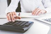 Elegant woman's hand is using calculator