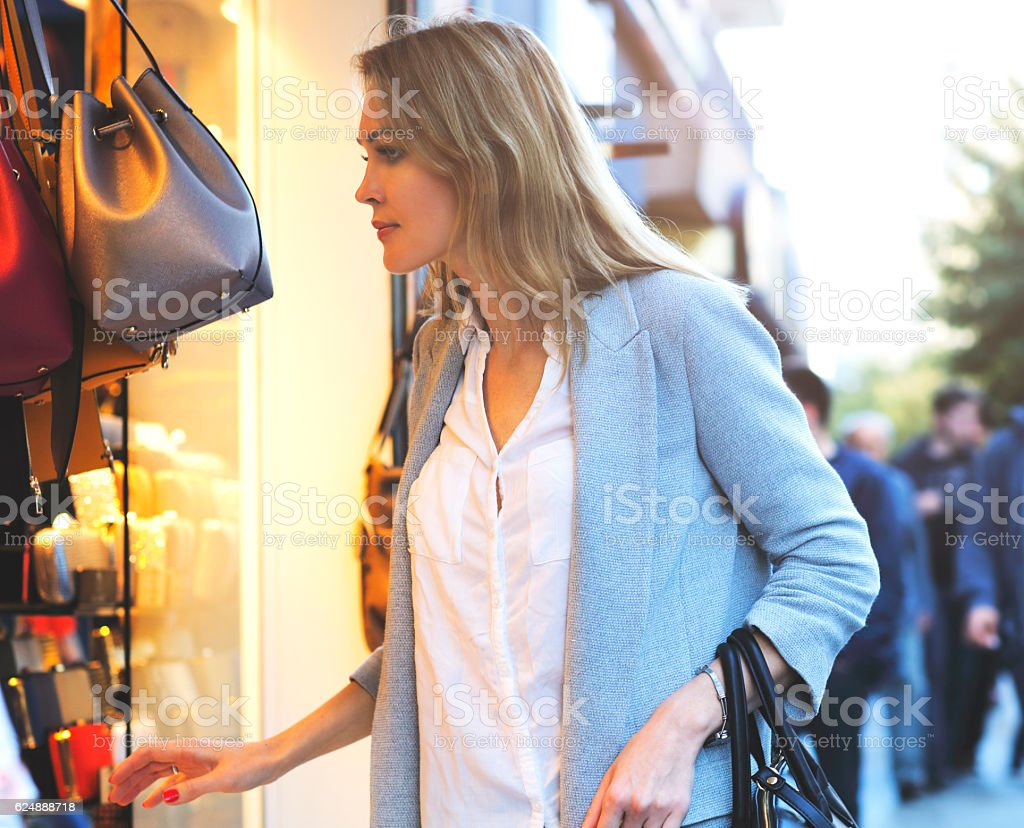 Elegant women looking through shop window stock photo