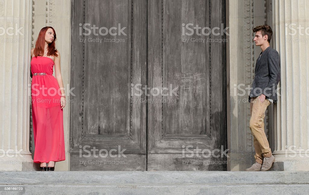 Elegant young couple separated by big wooden door stock photo