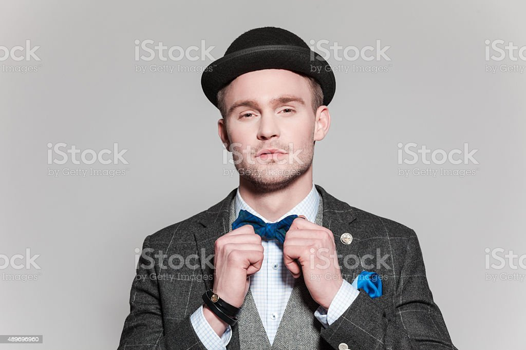 Elegant young man wearing tweed jacket, bow tie and hat stock photo