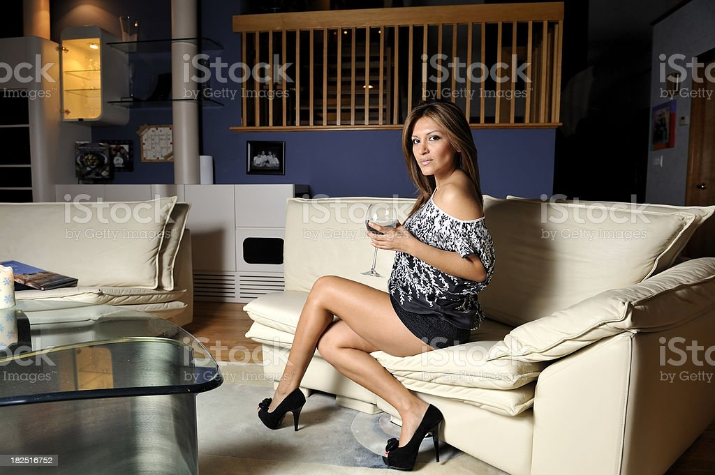 Elegant  young woman holding glass of wine in living room stock photo