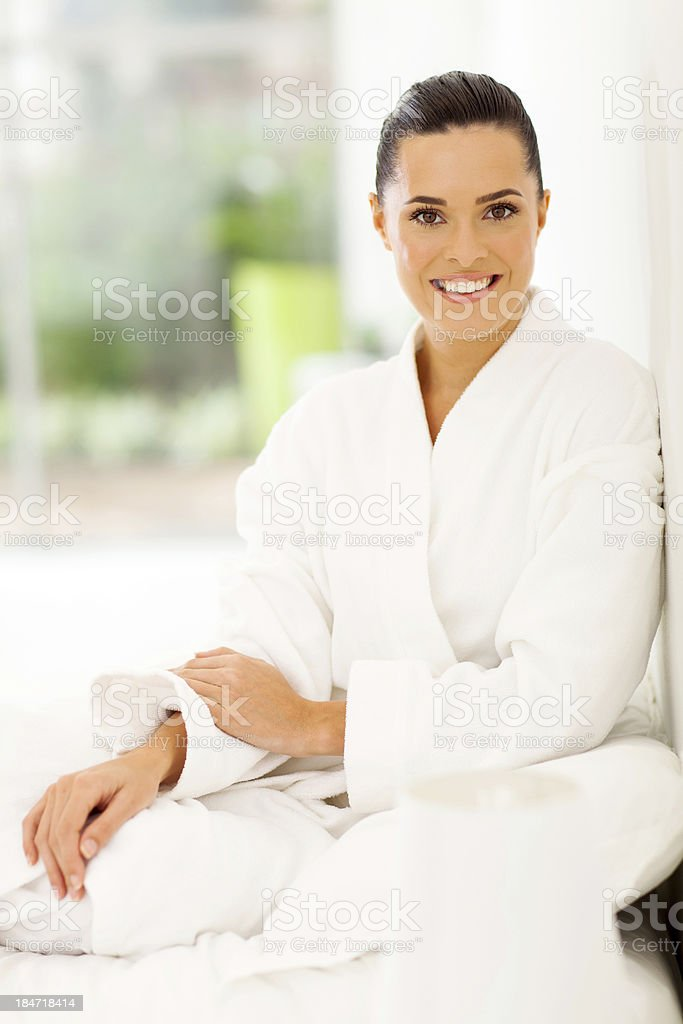 elegant young woman in bathrobe sitting on bed royalty-free stock photo