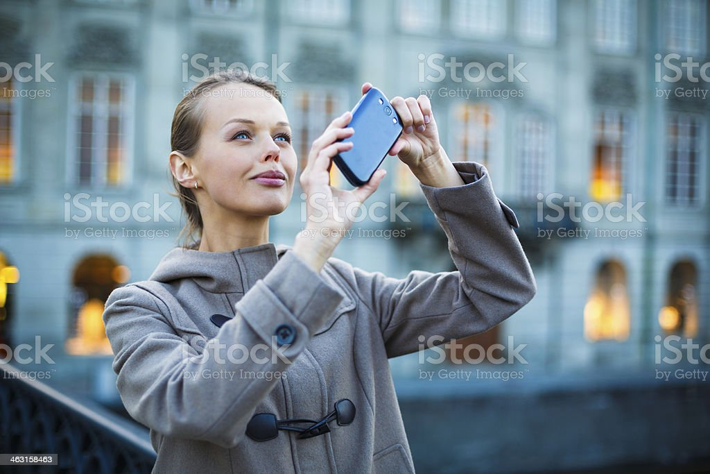 Elegant, young woman taking a photo stock photo