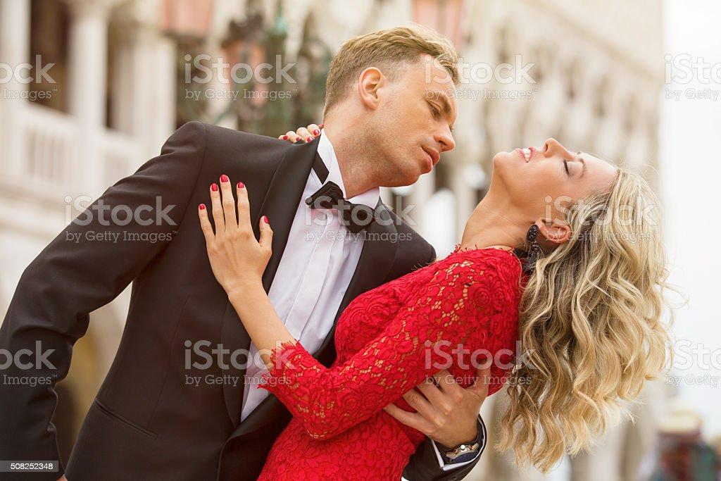Elegantly dressed couple dancing outside stock photo