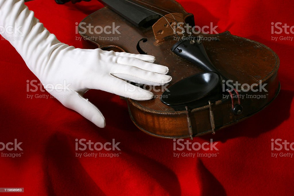 Elegantly gloved hand caresses an antique violin. royalty-free stock photo