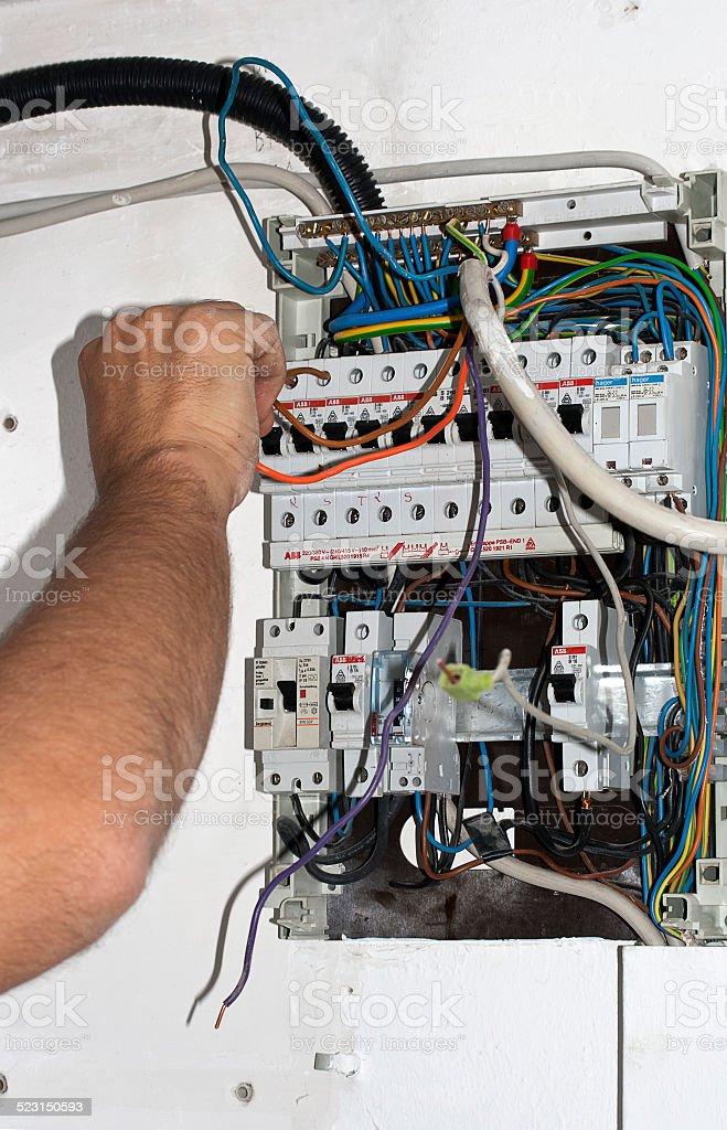 Elektriker schlie?t Kabel am Strom Kasten an stock photo