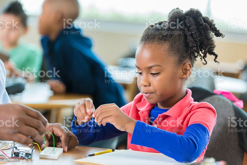 Elementary age African American girl building robot in science club stock photo