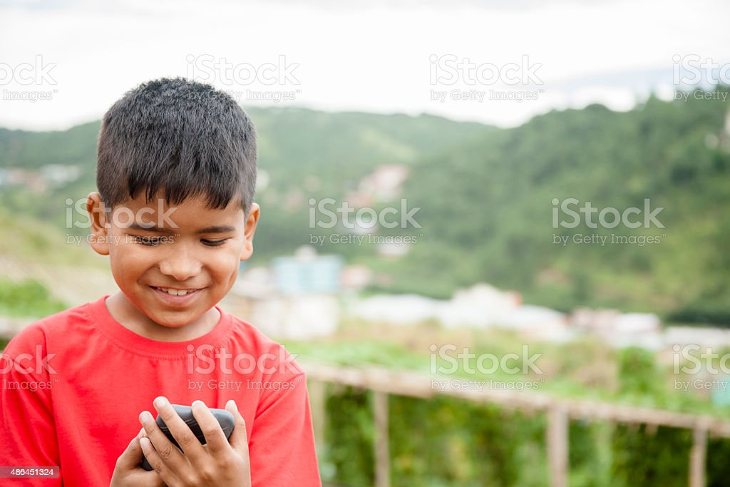 Elementary age, Asian boy using smart phone outdoors. Rural. stock photo