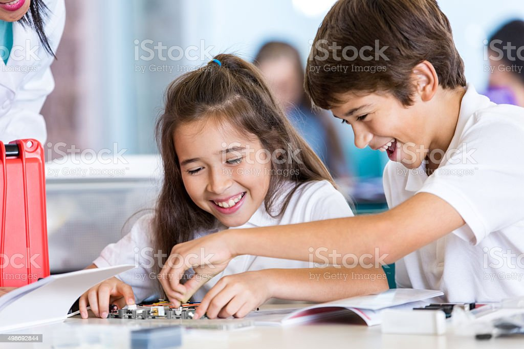 Elementary age boy and girl working on roobtics project stock photo