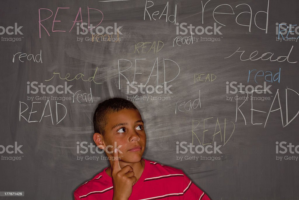 Elementary age boy in front of chalkboard with 'read' royalty-free stock photo