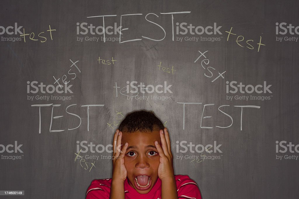 Elementary age boy in front of chalkboard with test anxiety royalty-free stock photo