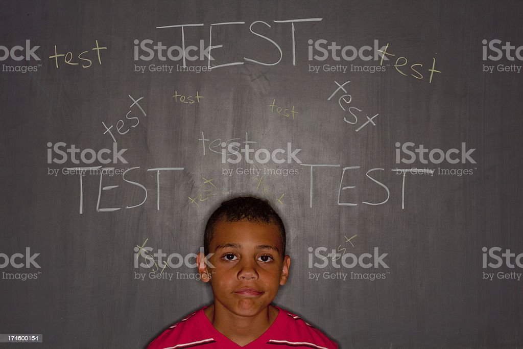Elementary age boy in front of chalkboard with 'test' royalty-free stock photo