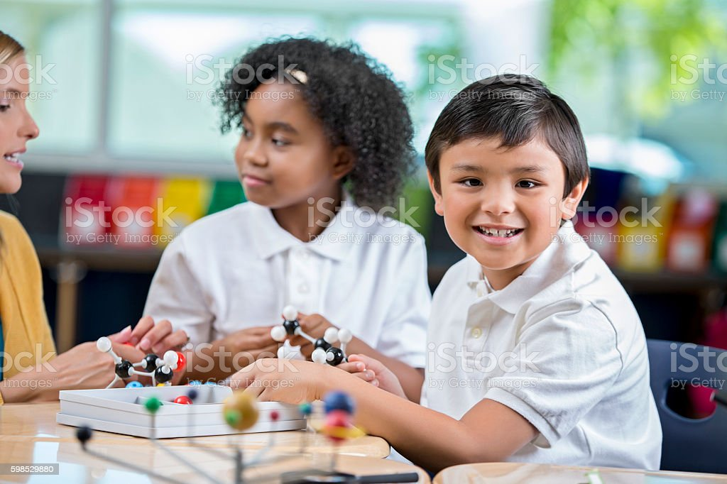 Elementary age boy in science class playing with molecule model stock photo