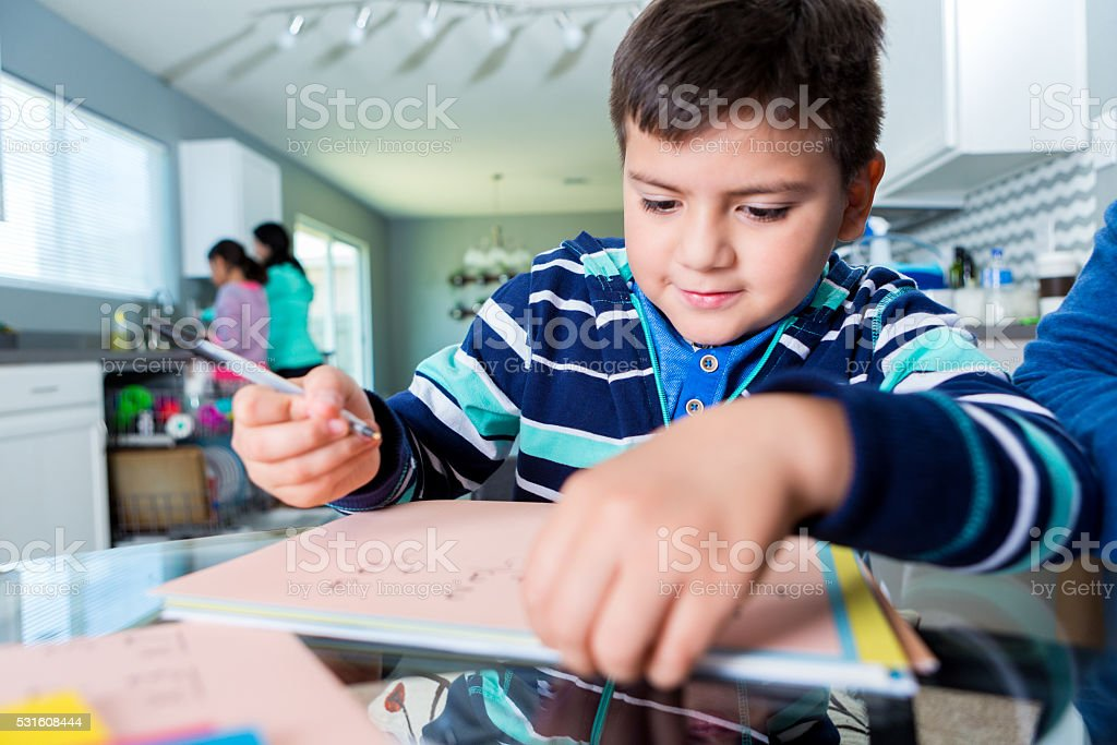 Elementary age boy works on homework assignment stock photo