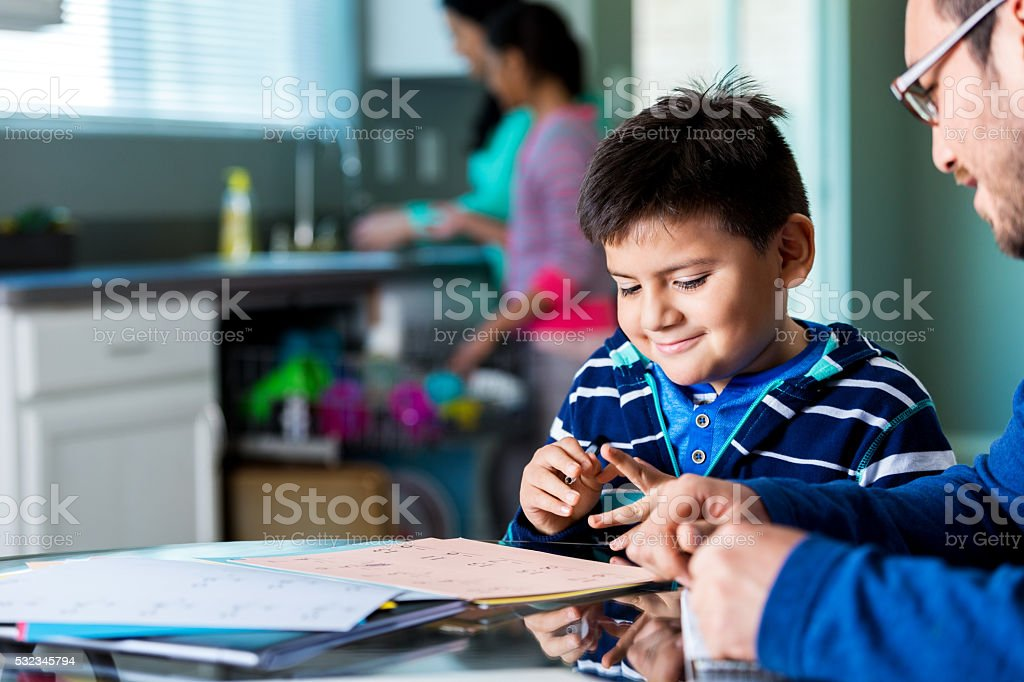 Elementary age boy works on homework with dad stock photo