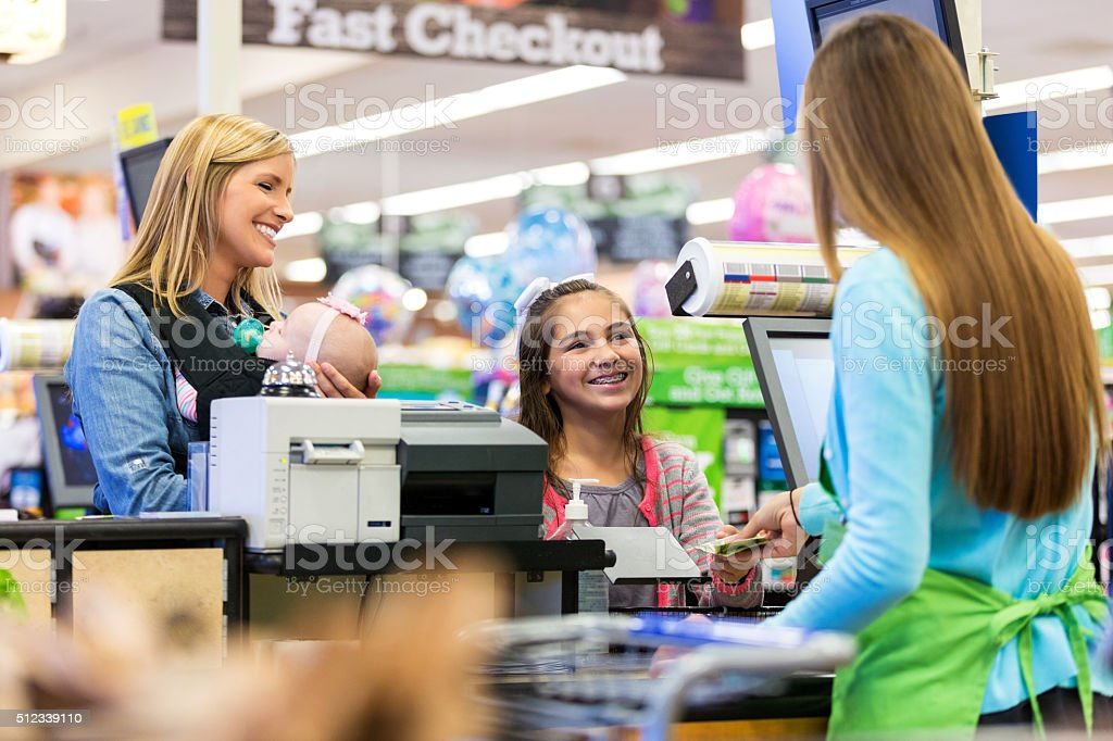 Elementary age customer using cash to pay for supermarket purchases stock photo