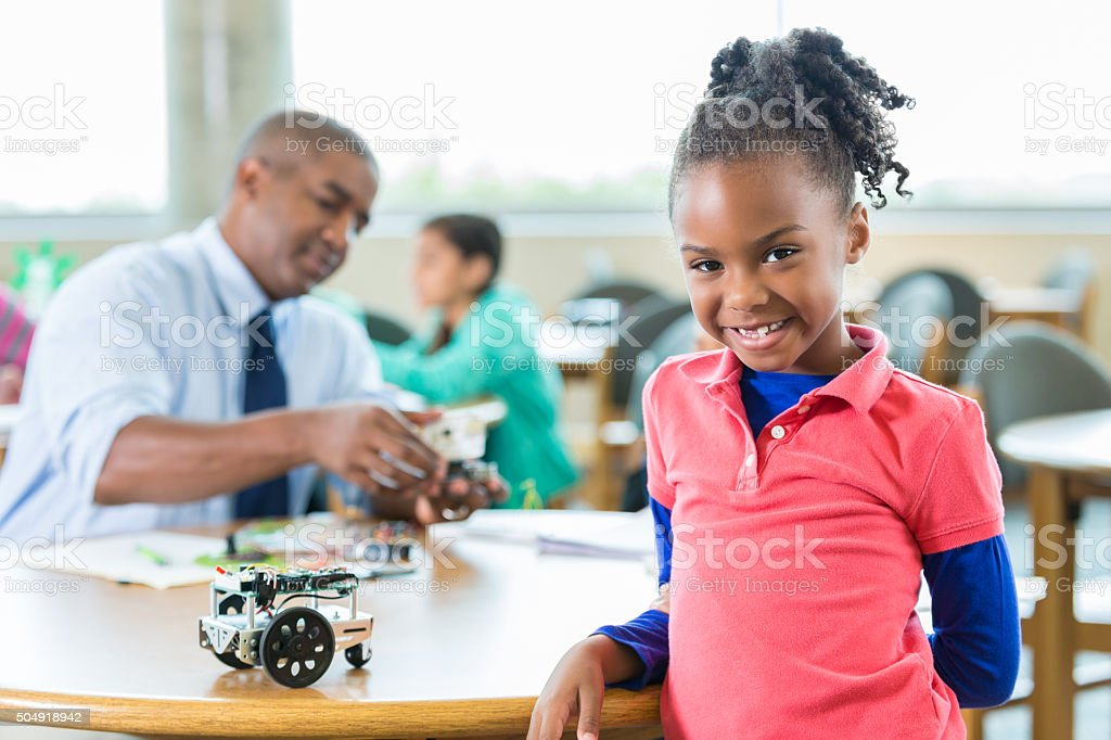 Elementary age girl in robotics science club after class stock photo