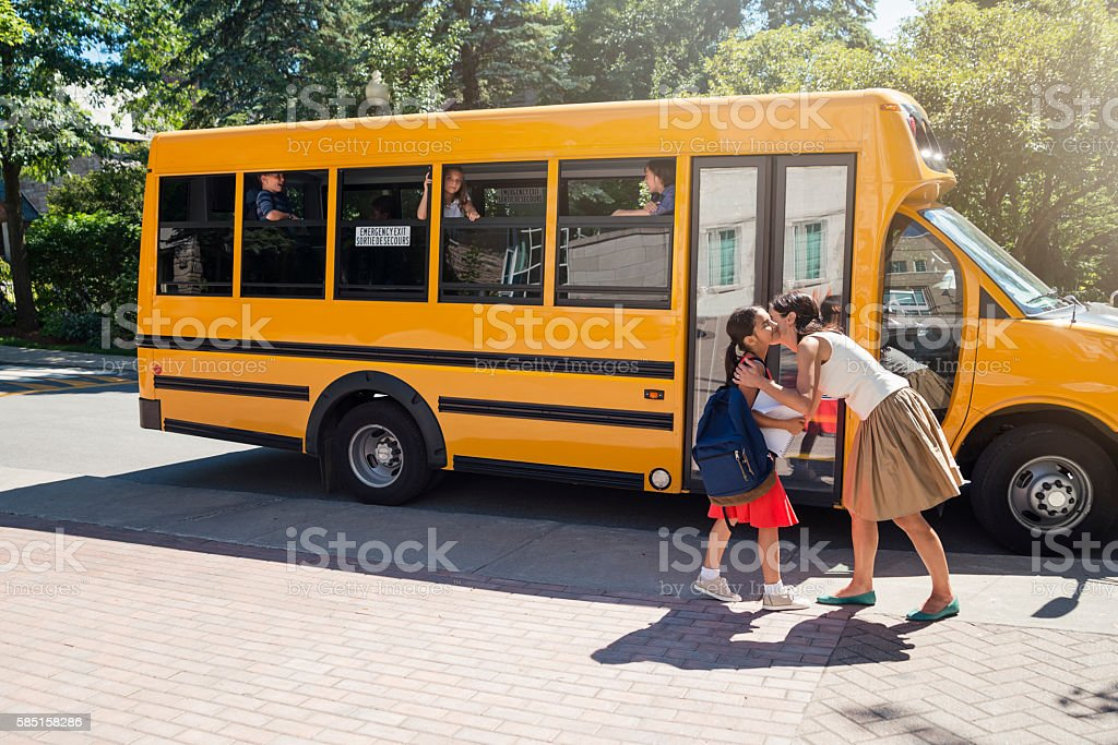 Elementary age girl kissing mother before getting on school bus. stock photo