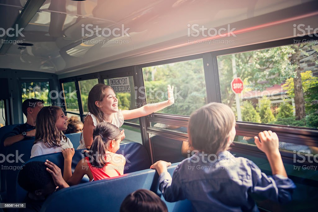 Elementary age girl saying hello from a school bus. stock photo