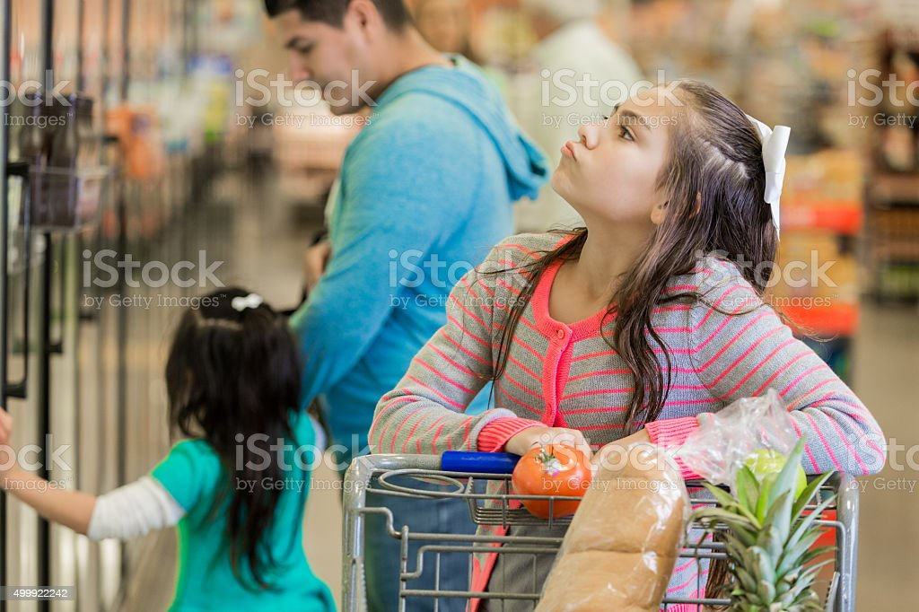 Elementary age girl shopping for groceries in supermarket with parents stock photo