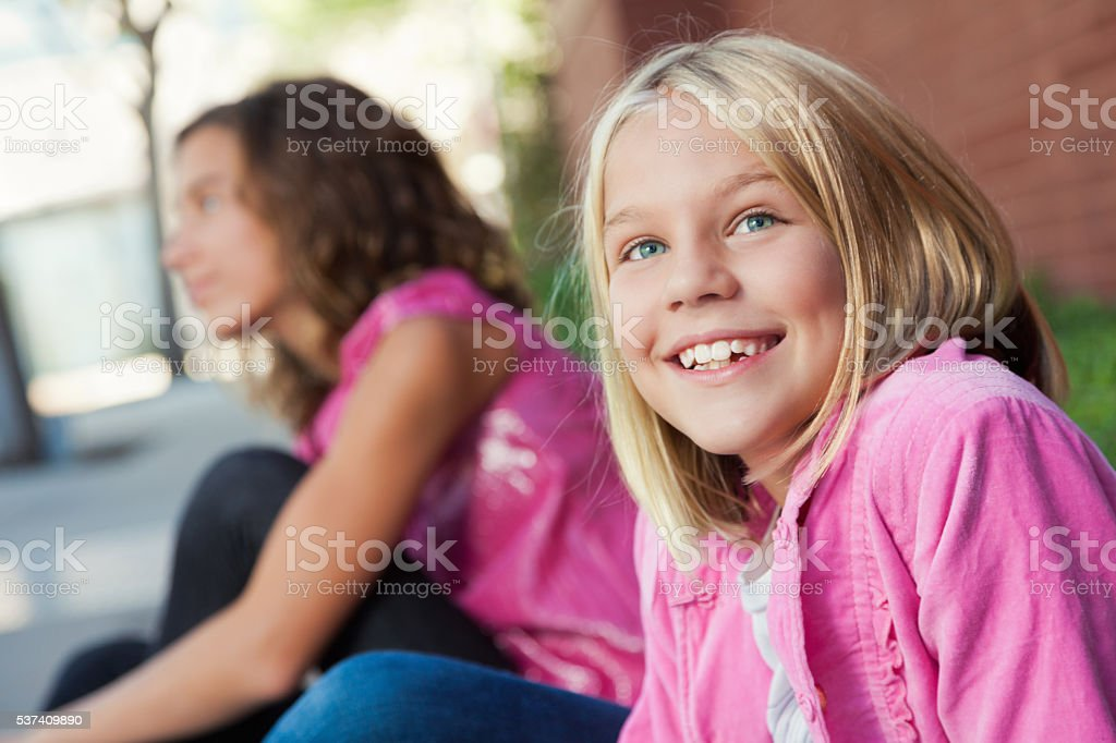 Elementary age girl sits outside of school stock photo
