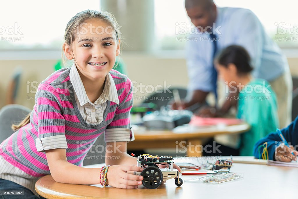 Elementary age girl smiling while using robotics in science class stock photo