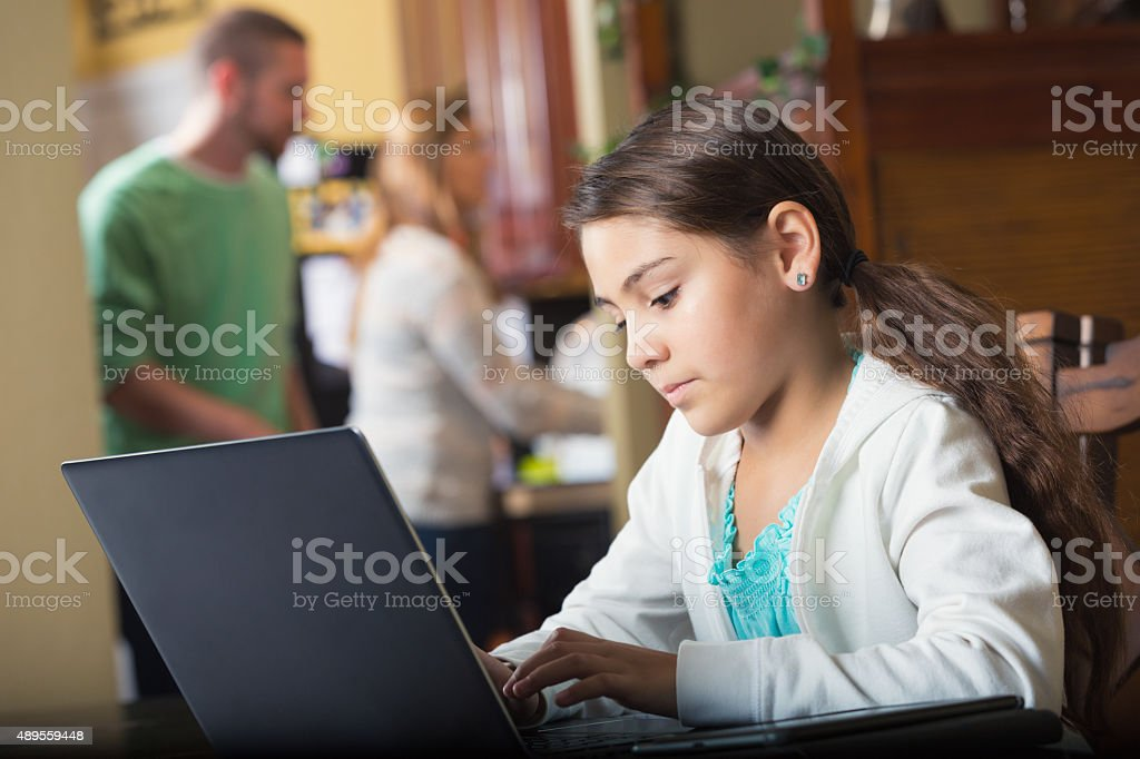 Elementary age girl using laptop computer at home stock photo