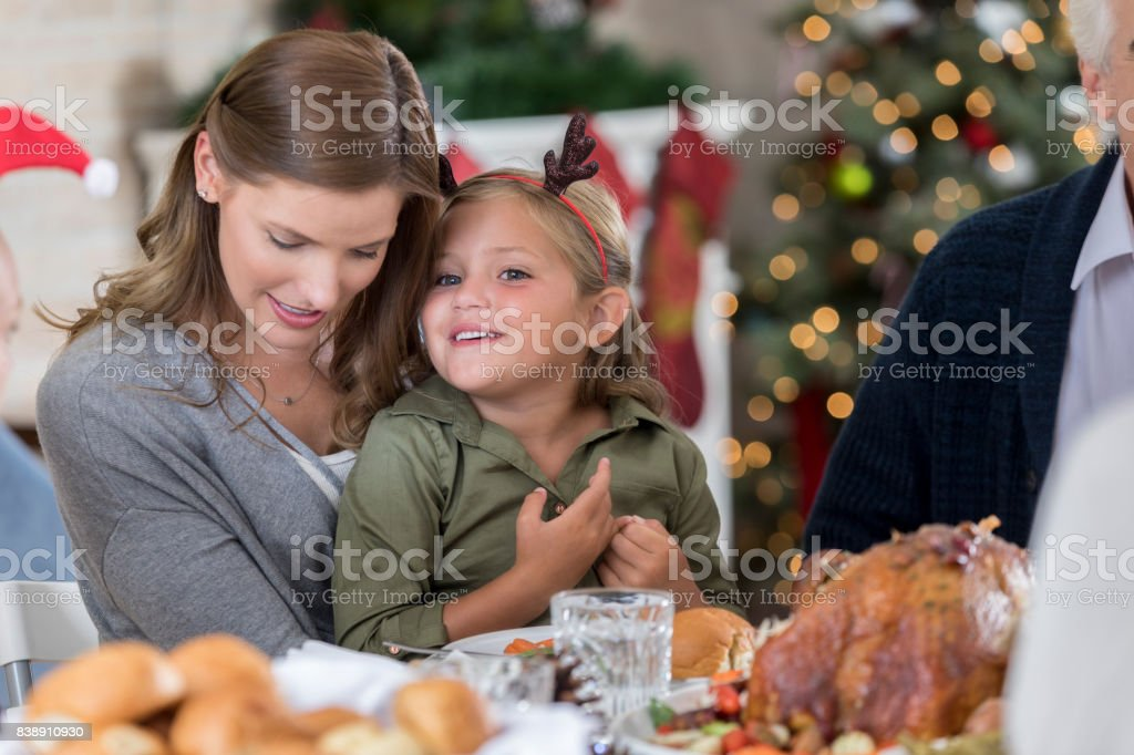 Adorable young girl whispers something in her mom\'s ear while they...
