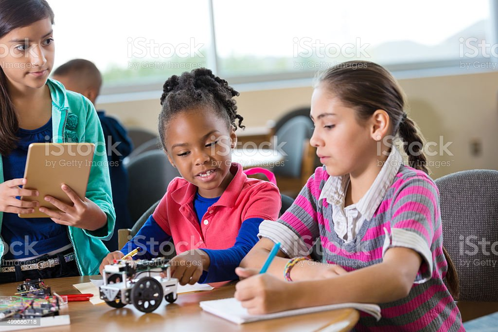 Elementary age girls building robot during robotics science class stock photo