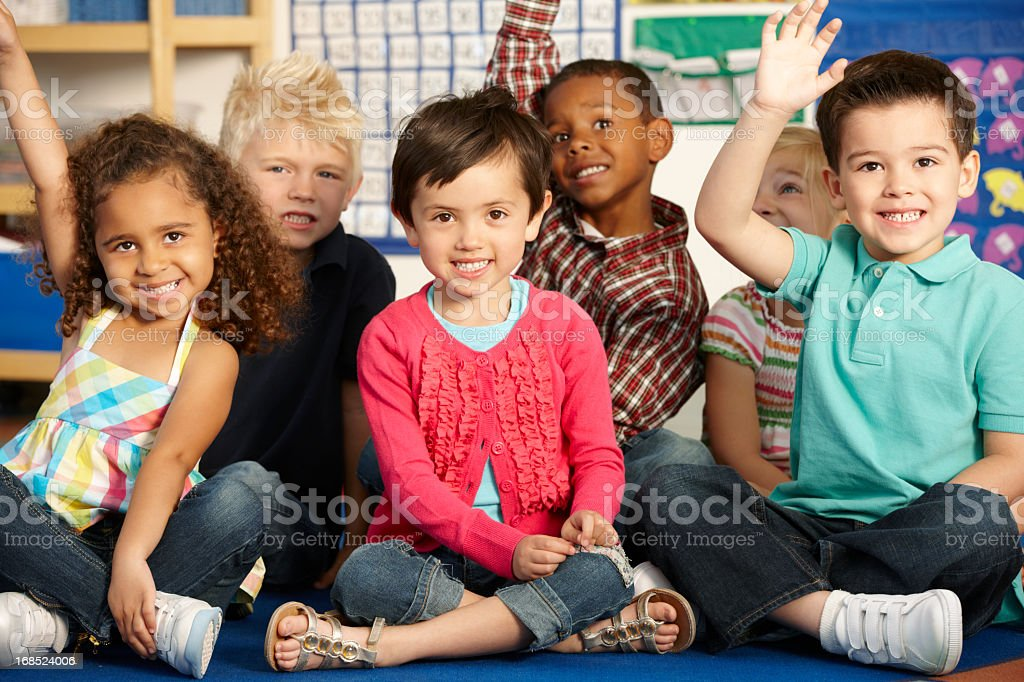 Elementary Age Schoolchildren Answering Question In Class stock photo