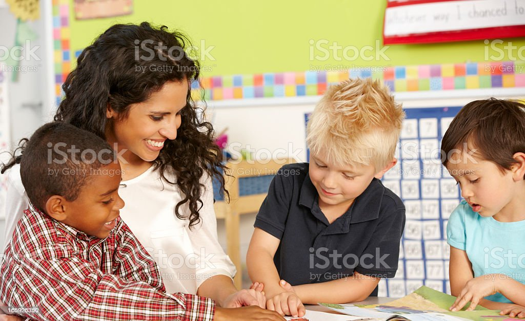 Elementary Age Schoolchildren In Class With Teacher stock photo